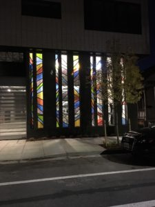 Evening light shows off the glass art John Tess created for Portland's Muse apartment complex.